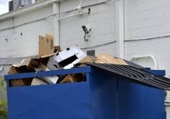 A small dumpster filled to the brim with cardboard boxes in a parking lot in Southeast Texas.